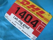 Et billede af et DHL Stafet løbenummer, der sidder fast på en løbe t-shirt.