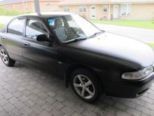 Matsort Mazda 626 fra 1995 står i et vognly