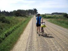 Druide trækker cyklen på grusvej