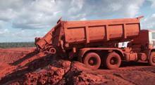 Et billede af en lastvogn som læsser en giftig rød substans i regnskoven. Et biprodukt fra aluminiumsproduktion.