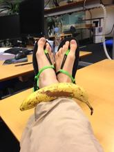 Fødder iklædt sandaler på kontoret - en banan ligger også på fødderne
